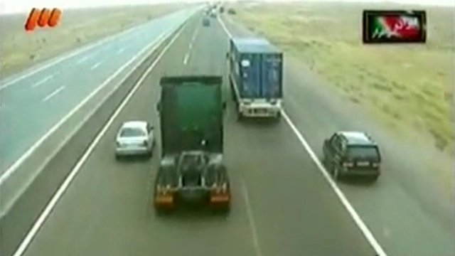 Iranian driver taking over on the hard shoulder from two trucks - whilst racing against the car on the left lane.