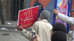 Egyptian protester holds up McDonald's sign as protection