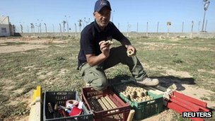 An employee of the Aman Society for demining and removal of war ordnance shows landmines that were planted by Gaddafi forces near Mitiga airport in Tripoli - 16 November 2011