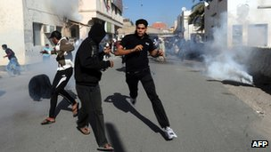 Protesters run for cover as Bahraini police fire tear gas (14 February 2011)