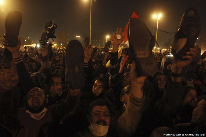 Protesters show the soles of their shoes as they chant slogans