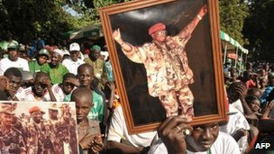 Supporters of Gambian President Yahya Jammeh hold picture of him on 22 November 2011 during a campaign meeting in Bakau