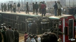 Government officials look at a passenger train which derailed in Kashmir on 23 November 2011
