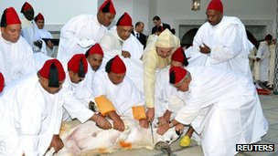 Morocco's King Mohammed VI (in gold robes) slaughters a sheep during the Muslim holiday of Eid al-Adha in Rabat 7 November, 2011.