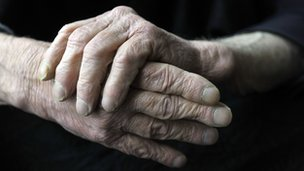An older person clasping their hands