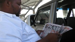 A South African minibus taxi driver reading a newspaper