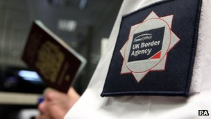 Border agency worker checking a passport