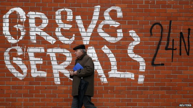 "A man walks near graffiti reading ""General Strike"" in Lisbon"
