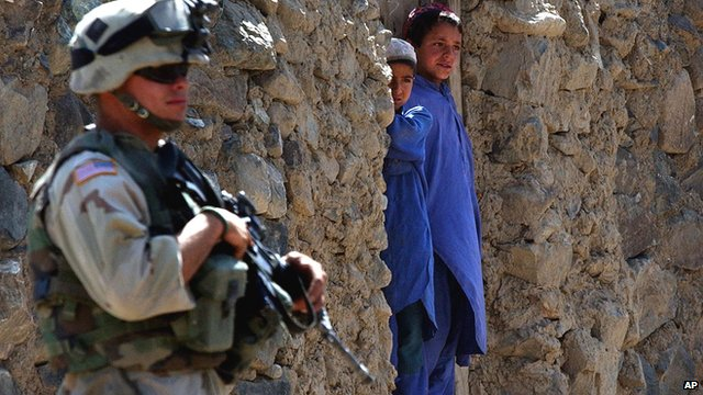 US Soldier (L) stands next to Afghan Children in a doorway (R)