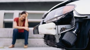 A woman sitting at the side of the road with her head in her hands and the smashed front end of a car.