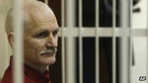Ales Belyatski sits in a cage in court in Minsk, 24 November 2011