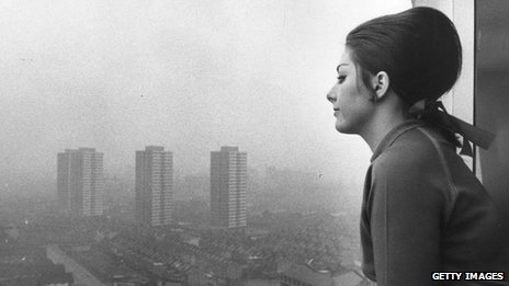 Woman looks out from London tower block