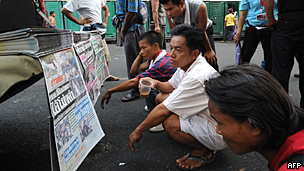 Thai men read newspapers in downtown Bangkok