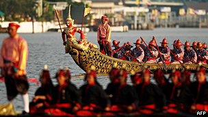 Thai Royal navy oarsmen in ancient warrior costume row the Royal barge on the Chao Phraya river during the Royal celebrations in 2007