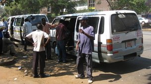 People standing by mini bus taxis in Harare, Zimbabwe