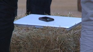 A Macbook and Blackberry on a bale of hay bale