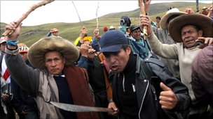 Peruvian protesters brandishing sticks and machetes