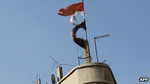 A torn Syrian flag fluttering on top of a building in the flashpoint city of Homs (24 Nov 2011)