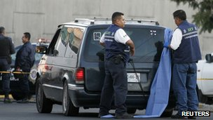 Forensic workers prepare to cover the window of a car with several dead bodies inside in Guadalajara on 24 November 2011