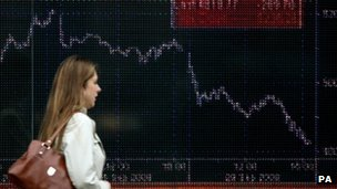 Woman walks past share index screen
