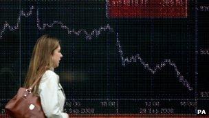 Woman walks past share index screen