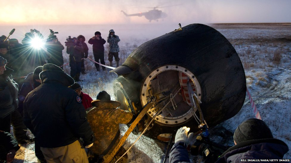 Russian support personnel work to help get Expedition 29 crew members out of the Soyuz TMA-02M spacecraft shortly after the capsule landed outside of the town of Arkalyk, Kazakhstan