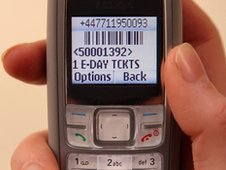 a rail passenger's mobile phone displays a barcode representing a purchased ticket