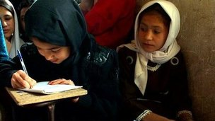 An Afghan girl writes during Dari language lesson at a school