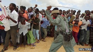 A member of al-Shabab controls residents as they participate in a demonstration against Kenya&#039;s incursion inside Somalia in Elasha, outside Mogadishu, on October 2011