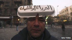 "A protester wearing a sign reading ""freedom or martyrdom"" in Arabic, near Tahrir Square, Cairo, 23 November 2011"