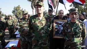 Syrian soldiers attend a group funeral on November 26, 2011 of comrades reportedly killed in an ambush by an armed group in the flashpoint Syrian city of Homs