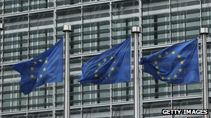 European Union flags blow in a breeze outside one of the buildings of the European Commission