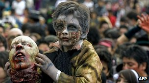 Mexican boy dressed as a zombie holding a fake severed head