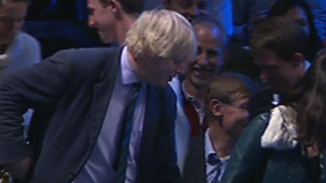 A sheepish Boris Johnson returns to his seat at the O2 Arena