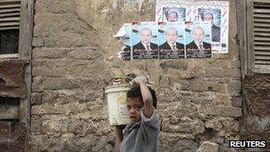 A boy carries water past election posters in Cairo (27 Nov 2011)