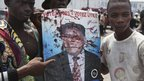 Opposition UDPS members hold up a blood-splattered poster of leader Etienne Tshisekedi after the presidential guard opened fire on the crowd outside N'Djili airport