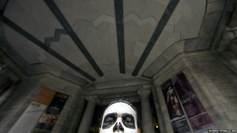 A man with his face painted as a skull attends a protest against violence, Mexico City