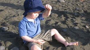 Child plays on dark sand beach