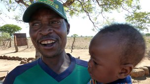 Shadrack Rwafa holding a baby