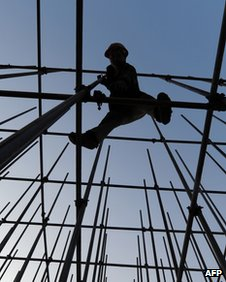 Worker stands on scaffolding for new shopping mall in Hefei, Anhui province, on 27 November 2011