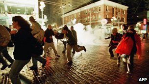 On 1 December 1999, Seattle police fire tear gas to clear the streets