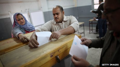 Election official (left) helps a man to put voting paper in ballot box, Cairo, 28.11.2011