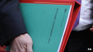 George Osborne holding the Autumn Statement document