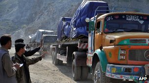"Pakistani security personnel chat with a truck driver carrying supplies for NATO forces in Afghanistan returning from Pakistan""s Torkham border crossing after Pakistani authorities shut vital NATO supply routes on November 28, 2011."