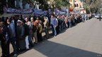 Egyptians queue outside a polling station in the Heliopolis suburb of Cairo