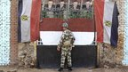 An Egyptian soldier stands guard in front of a polling station during the parliamentary election in Cairo