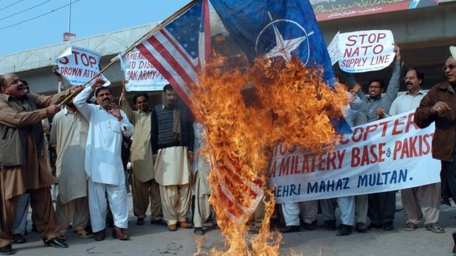 Pakistani protesters burn a US and Nato flag during a protest in Multan
