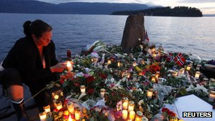 A woman lights a candle to pay her respects to the victims of the shooting spree and bomb attack in Norway, on the shore in front of Utoeya island, northwest of Oslo, 26 July