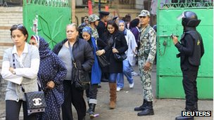 Egyptians stand in line at a polling station as they wait to cast their votes during parliamentary elections in Cairo