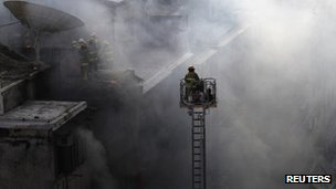 Firefighters rescue people from the roof of a building at the Fa Yuen Street fire scene in Hong Kong, 30 Nov 2011
